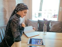 Muslim woman working in cafe. Beautiful muslim woman writing on paper at cafe Royalty Free Stock Photos