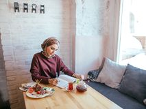 Muslim woman working in cafe. Beautiful muslim woman writing on paper at cafe Stock Image