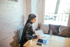 Muslim woman working in cafe. Muslim woman wearing red scarf writing beside notebook at cafe Royalty Free Stock Photography