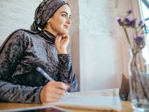 Muslim woman working in cafe. Muslim woman writing love diary in cafe Royalty Free Stock Images