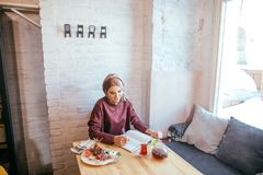 Muslim woman working in cafe. Writing on notepad Royalty Free Stock Images