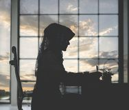 Muslim woman working on office table silhouette with sunset stock images