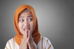 Muslim Woman Worried, Nervous and Looking to the Side. Portrait of young Asian muslim woman looks worried and nervous looking to the side, afraid of something royalty free stock images