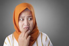 Muslim Woman Worried, Nervous and Looking to the Side. Portrait of young Asian muslim woman looks worried and nervous looking to the side, afraid of something royalty free stock image