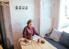Muslim woman working in cafe. Muslim woman writing love diary in cafe Stock Photography
