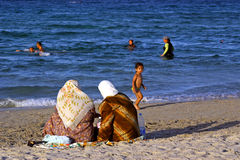 Muslim women. Some Muslim women on the beach of Mahdia in Tunisia stock image