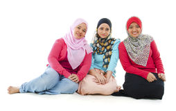 Muslim women. Portrait of three cheerful muslim women sitting on white background Royalty Free Stock Image