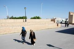 Muslim women. Kaioruan, Tunisia - September 16th, 2012 : Muslim women passing by the walls surrounding the  Great Mosque of Kairouan in the street of Kairouan Royalty Free Stock Image