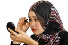Muslim women applying makeup. A muslim lady wearing headscarf and applying makeup - isolated on a white background Stock Photos