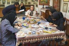 Muslim women artists in black headscarfs paint traditional Persian miniature in a workshop in Isfahan, Iran. ISFAHAN, IRAN - JUNE 25, 2007: Unidentified muslim Stock Image