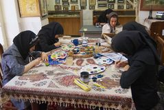 Muslim women artists in black headscarfs paint traditional Persian miniature in a workshop in Isfahan, Iran. ISFAHAN, IRAN - JUNE 25, 2007: Unidentified muslim Royalty Free Stock Photo