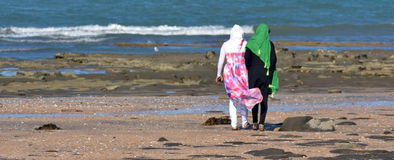 Muslim women. AUCKLAND, NZL - JAN 25 2015:Two muslim women on the beach.Over 130 million women and girls have experienced Female genital mutilation, 21% of Stock Images