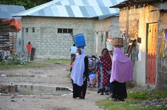 Muslim women carrying water in Zanzibar Royalty Free Stock Photos