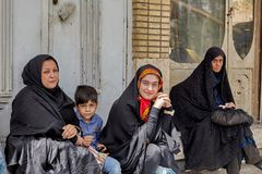 Muslim women with child sitting at bus stop, Kashan, Iran. Kashan, Iran - April 27, 2017: Three women dressed in black Islamic clothes, and one little boy royalty free stock images