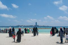 Muslim women and children walking towards ocean at the tropical beach Royalty Free Stock Image
