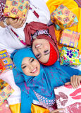 Muslim women with gifts. Two Muslim women surrounded by colorfully wrapped gifts or presents Royalty Free Stock Image