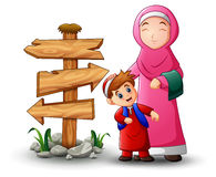 A Muslim women hold her son head and blank wood arrow sign. Illustration of A Muslim women hold her son head and blank wood arrow sign Royalty Free Stock Images