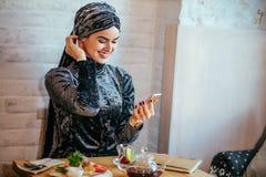 Muslim women holding smartphonephone. thinking of good memories. Royalty Free Stock Photography
