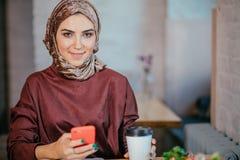 Muslim women holding smartphonephone. thinking of good memories. Royalty Free Stock Photos