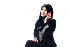 Muslim women on phone. A  muslim women on phone isolated white background Stock Image