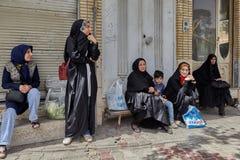 Muslim women`s group at bus stop waiting public transport, Iran. Kashan, Iran - April 27, 2017: A group of Muslim women at the bus stop is waiting for the Stock Photos