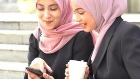 Muslim women using smart phone. Sharing and laughing stock video