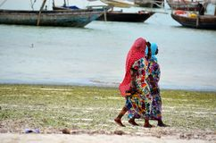 Muslim women walking at the beach, Zanzibar Stock Photo