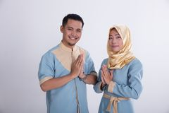 Muslim young couple greeting. Two beautiful young couple greeting using asian muslim gesture Royalty Free Stock Photography