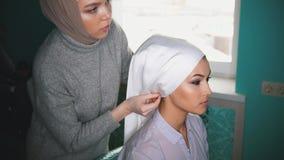 Muslim young woman preparing islamic wedding attire for beautiful bride. Muslim young women preparing islamic wedding attire for beautiful bride, close up Royalty Free Stock Photo