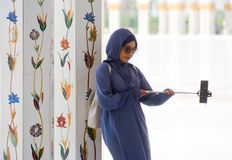Muslima making selfie. ABU DHABI, UNITED ARAB EMIRATES - DEC 28, 2017: A muslima is making a selfie with her smartphone in the Sheikh Zayed Mosque in Abu Dhabi Royalty Free Stock Image
