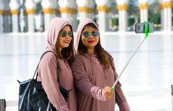 Muslima`s making selfie. ABU DHABI, UNITED ARAB EMIRATES - DEC 28, 2017: A muslima`s are making a selfie with their smartphone in the Sheikh Zayed Mosque in Abu Royalty Free Stock Photography