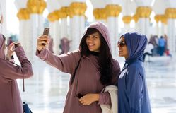 Muslima`s making selfie. ABU DHABI, UNITED ARAB EMIRATES - DEC 28, 2017: Veiled muslima`s are making a selfie with their smartphone in the Sheikh Zayed Mosque in Royalty Free Stock Photos