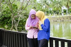 Muslimah享用室外,有讨论一致拿着手机的公园和他们 库存图片