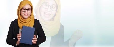 Muslimah affärskvinna Smiling som rymmer boken arkivbilder
