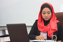 Muslimah business concept. Beautiful young muslim business woman working with files and laptop Stock Photography
