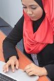 Muslimah business concept. Closeup of a young muslim woman using laptop Stock Photos
