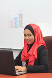 Muslimah business concept. Young asian muslim business woman smile to camera while using laptop Royalty Free Stock Photography