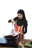 Muslimah concept. Beautiful muslim woman cooking healthy food in the kitchen isolated white background Stock Photo