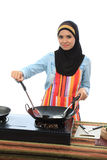 Muslimah concept. Beautiful muslim woman cooking and smile while looking to the camera in the kitchen isolated white background Royalty Free Stock Photography