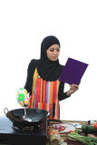 Muslimah concept. Beautiful muslim woman read the cook book while cooking in the kitchen isolated white background Royalty Free Stock Photography