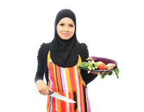 Muslimah concept. Beautiful muslim woman smile holding vegetables and knife while looking to the camera in the kitchen isolated white background Royalty Free Stock Photos