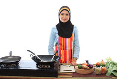 Muslimah concept. Beautiful muslim woman smile while looking to the camera in the kitchen isolated white background Stock Photo