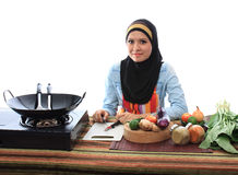 Muslimah concept. Beautiful muslim woman smile while looking to the camera in the kitchen isolated white background Royalty Free Stock Images