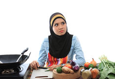 Muslimah concept. Beautiful muslim woman thinking while cutting chili in the kitchen isolated white background Stock Photo