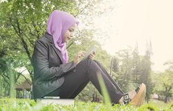 Muslimah student reading an e-book on her tablet.