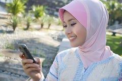 Muslimflickan använder handphone Fotografering för Bildbyråer