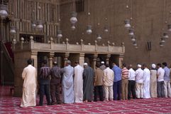 Muslims Praying in a Mosque, Islam Religion. Muslims gather to pray at the Sultan Hassan Mosque in Cairo, Egypt. This is the same mosque visited by President Stock Photo