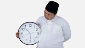 Muslimsk asiat med överviktigt anseende och att rymma fasta för avbrott för stor rund klocka väntande på kan den feta pojken för  royaltyfria bilder