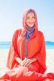 Muslimsk caucasian kvinna (för ryss som) bär den röda klänningen royaltyfria foton
