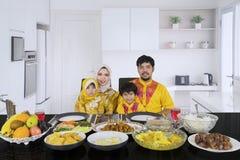 Muslimsk familj som har matställen i köket royaltyfria bilder